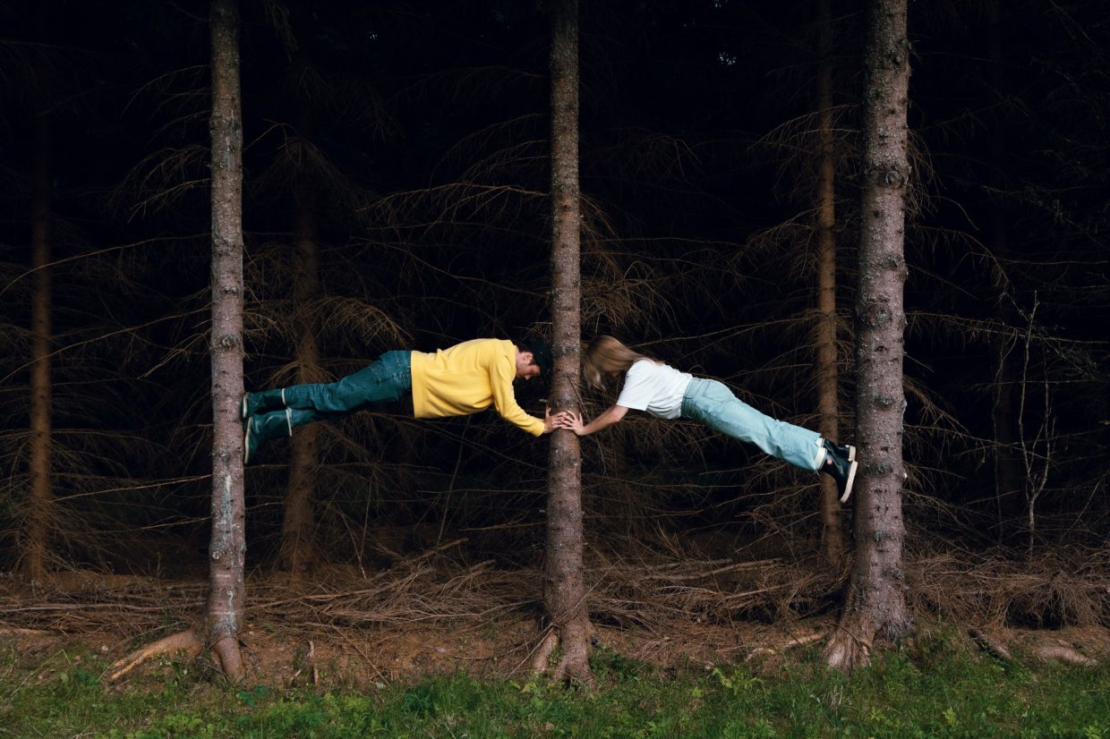 A man and a woman, dressed in rubber boots, climbing a tree in a dark forest.