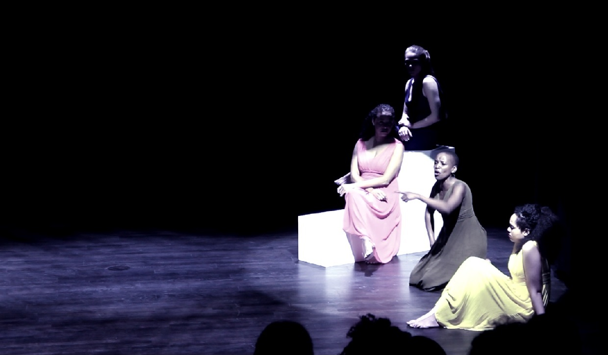 Actresses in long dresses sitting in the spotlight on a dark stage