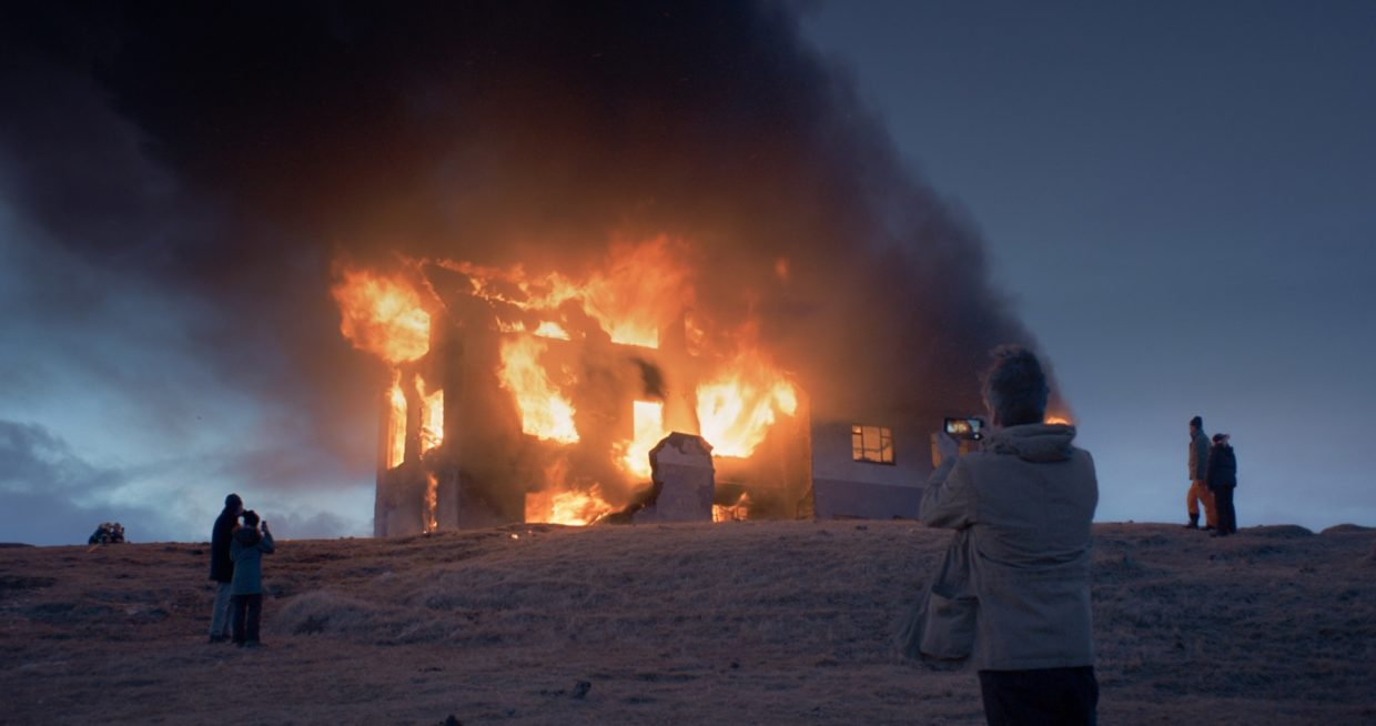 A burning house is being photographed by passers-by.