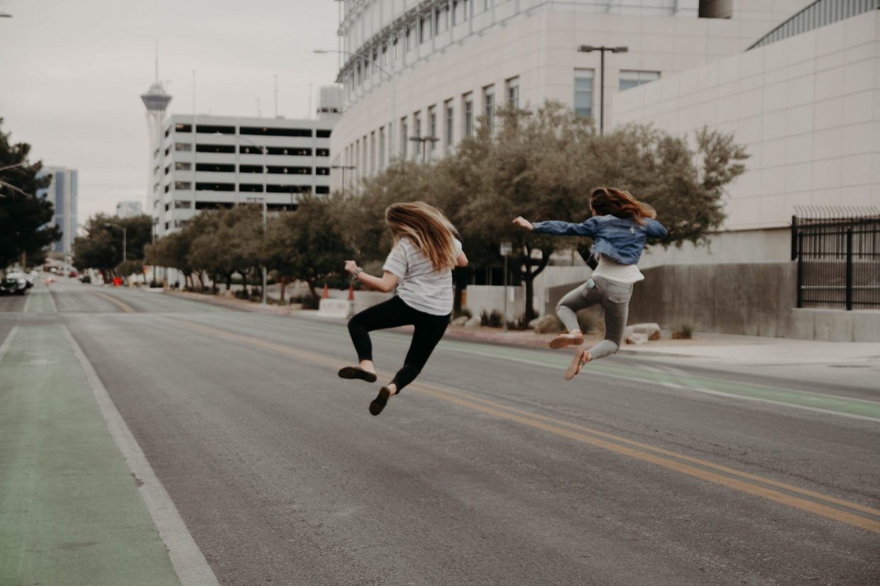 Two girls jumping in the street